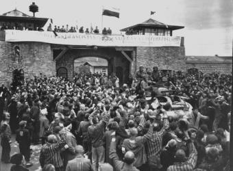 Prisioneros en Mauthausen reciben a las tropas que liberaron el campo en 1945. En la torre, una pancarta de los españoles.- NATIONAL ARCHIVES