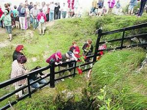 Varias personas arrojan claveles a la sima de Funeres. fernando rodríguez