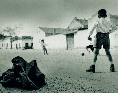 Tres niños juegan al fútbol en Aranjuez con una chaqueta como portería. La imagen fue tomada en marzo de 1948. - fotografías de Vicente Nieto Canedo