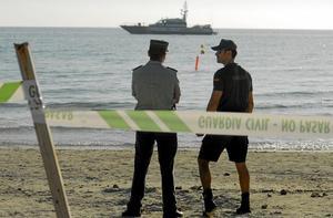 Agentes vigilan la playa precintada, mientras una boya señaliza el lugar donde apareció la bomba. Foto: JOAN LLADO